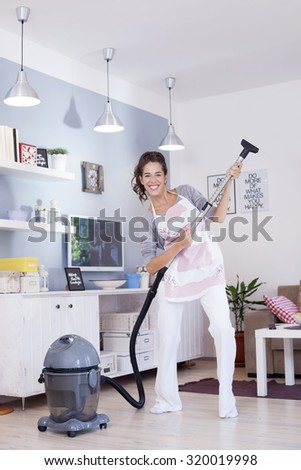 Young excited woman cleaning with a vacuum cleaner and pretending to be playing guitar  - stock photo
