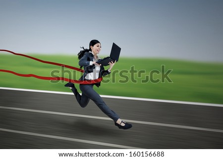 Young executive businesswoman running and holding a laptop on finish line - stock photo
