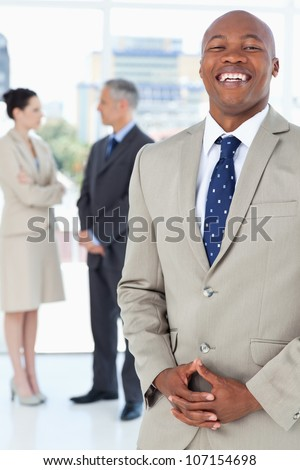 Young executive laughing while standing upright and crossing his hands - stock photo