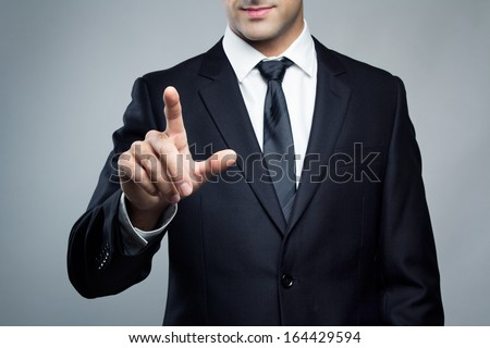 Young executive man touching an imaginary screen - stock photo