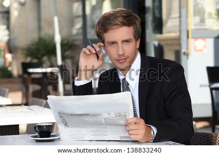 Young executive reading a newspaper in a cafe - stock photo