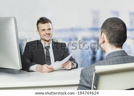 Young executive satisfied with the performance of the employee - concept - stock photo