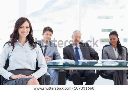 Young executive sitting with her hand on her leg and accompanied by her team in the background