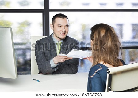 Young executive smiling, issuing orders to its employee - stock photo