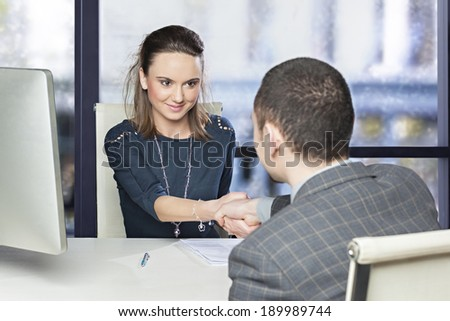 Young executive smiling shaking hands to its employee  - stock photo