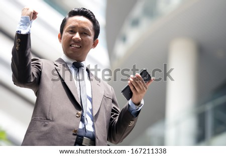 Young executive using tablet phone outdoor with success expression - stock photo