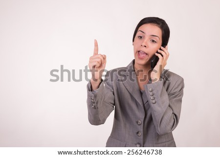 Young executive woman dressed in grey and with a cellular by providing guidance by phone and finger pointing upward - stock photo