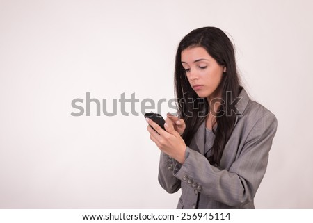 Young executive woman dressed in grey and with a cellular texting - stock photo