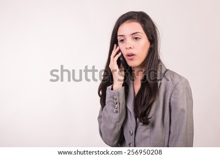 Young executive woman dressed in grey with a cellular giving orders and orientations - stock photo