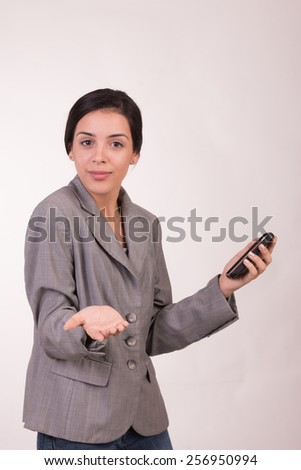 Young executive woman dressed in grey with a cellular looking at the camera and a gesture of questions - stock photo