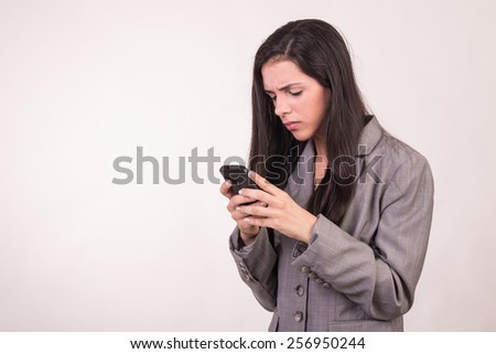 Young executive woman dressed in grey with a cellular looking down and texting - stock photo