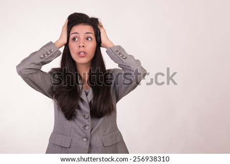 Young executive woman dressed in grey with a cellular looking up and her hands on her head regretting - stock photo