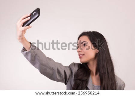 Young executive woman dressed in grey with a cellular taking a photo herself - stock photo