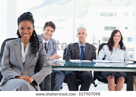 Young executive woman smiling while sitting with her legs crossed and her hands on her leg - stock photo