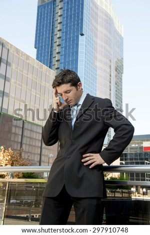 young exhausted and worried businessman standing outdoors on street in front of business buildings at financial district looking desperate and sad in work stress and depression concept