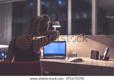 Young exhausted,depressed,concentrated woman sitting in her room or office with french windows  in the dark at the lamp.Studies late at night.Staying up late. Overworking. Feeling pain in the neck - stock photo