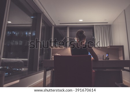 Young exhausted,depressed,concentrated woman sitting in her room or office with french windows  in the dark at the lamp.Studies late at night.Staying up late. Overworking.  - stock photo