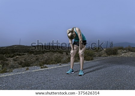 young exhausted sport woman running outdoors on asphalt road in mountain landscape stop for breathing after huge effort in fitness workout training shot in dramatic advertising style - stock photo