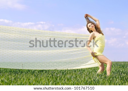 Young expressive beautiful woman in a green field
