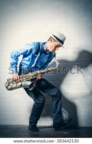 Young expressive musician playing the saxophone. Art and music. Jazz music. - stock photo