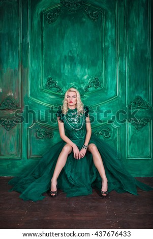 Young extravagant beautiful woman in the studio with hair and professional make-up in green queen vintage dress, bright red lips, blonde, thin waist, beautiful figure, fashion, magazine shooting