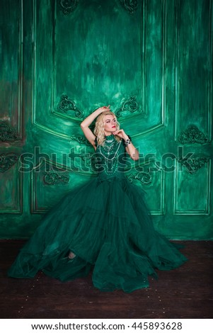 Young extravagant beautiful woman in the studio with hair and professional make-up in green vintage dress, bright red lips, blonde, thin waist, figure, fashion, magazine shooting