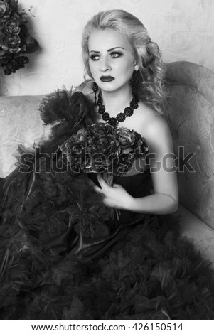 Young extravagant woman sitting on sofa in a beautiful vintage dress with spring flowers and  looking to the right. Retro style. Black and white studio shot - stock photo