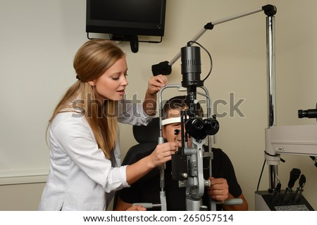 Young eye Doctor druring a test with patient in her office - stock photo