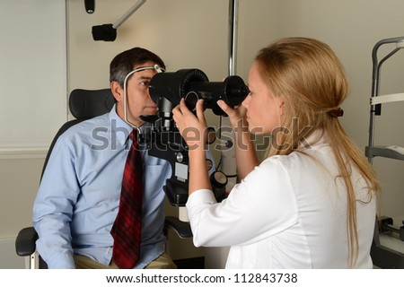 Young Eye Doctor with her patient during an examination - stock photo