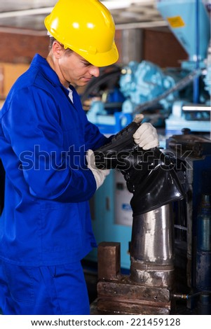 young factory worker making gumboot - stock photo