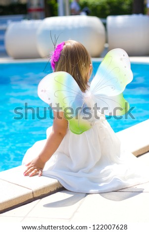 Young fairy dreaming near the pool - stock photo