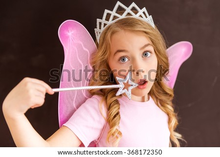 Young fairy in a pink shirt with a white crown on her head and pink wings holding a magic wand at face - stock photo