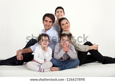Young family all sat on the floor - stock photo