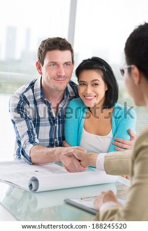 Young family and broker making a deal - stock photo