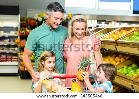 Young family behind their trolley at supermarket - stock photo