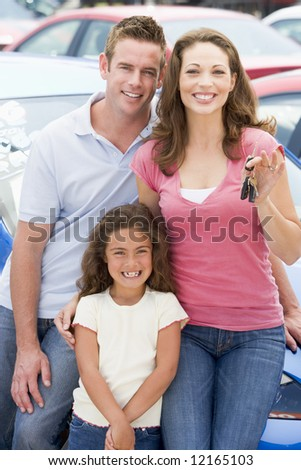 Young family collecting new car from lot