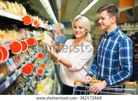 Young family couple choosing chilled sausages in shop - stock photo