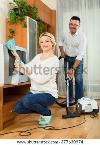 Young family couple cleaning at home together and smiling - stock photo
