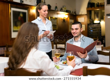 Young family couple eating out in a tavern. Man is holding a menu in his hands while his girlfriend is taking a sip from a glass of wine - stock photo