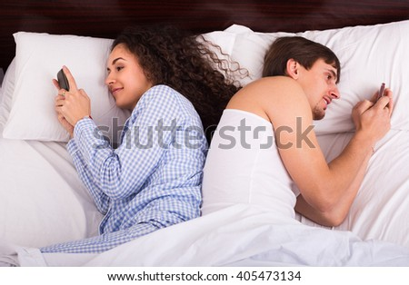 Young family couple in bed busy with mobile phones separately 