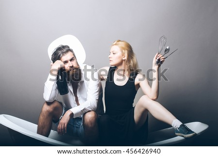 young family couple of blonde pretty girl with kitchen utensils and bearded man with long beard holding wine bottle sitting on bathtub on grey background. household, everyday life and routine