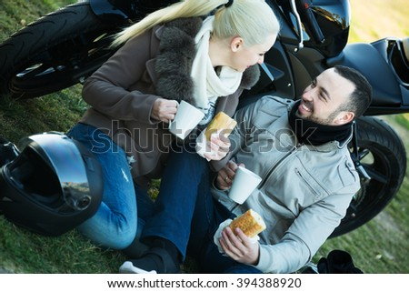 Young family couple posing near motor bike with sandwitches and coffee and smiling - stock photo