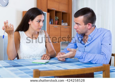 Young family couple with money problems making shopping list at home - stock photo
