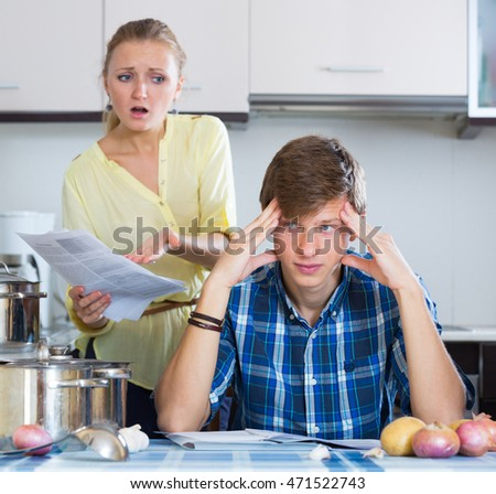 Young family couple with serious faces quarrelling in kitchen