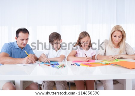 Young Family Drawing Together With Colorful Pencils And Crayons At Home
