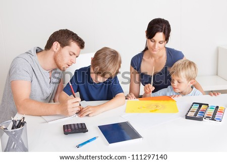 Young family drawing together with colorful pencils at home - stock photo