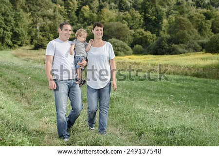 Young family enjoying forest and tranquil nature - stock photo