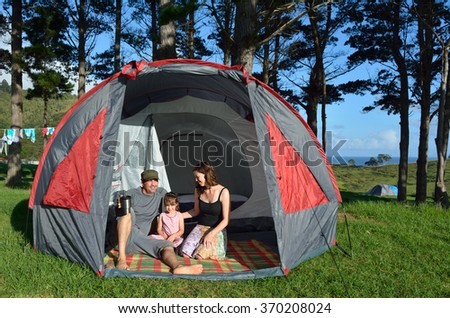 Young family, father and mother with one child (girl) camping in a tent outdoors. - stock photo