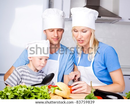 young family; father, mother and their five year old son cook together in the kitchen at home