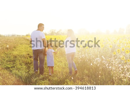 Young family (father,mother,daughter) is on the field where the sunflowers grow on a bright Sunny day